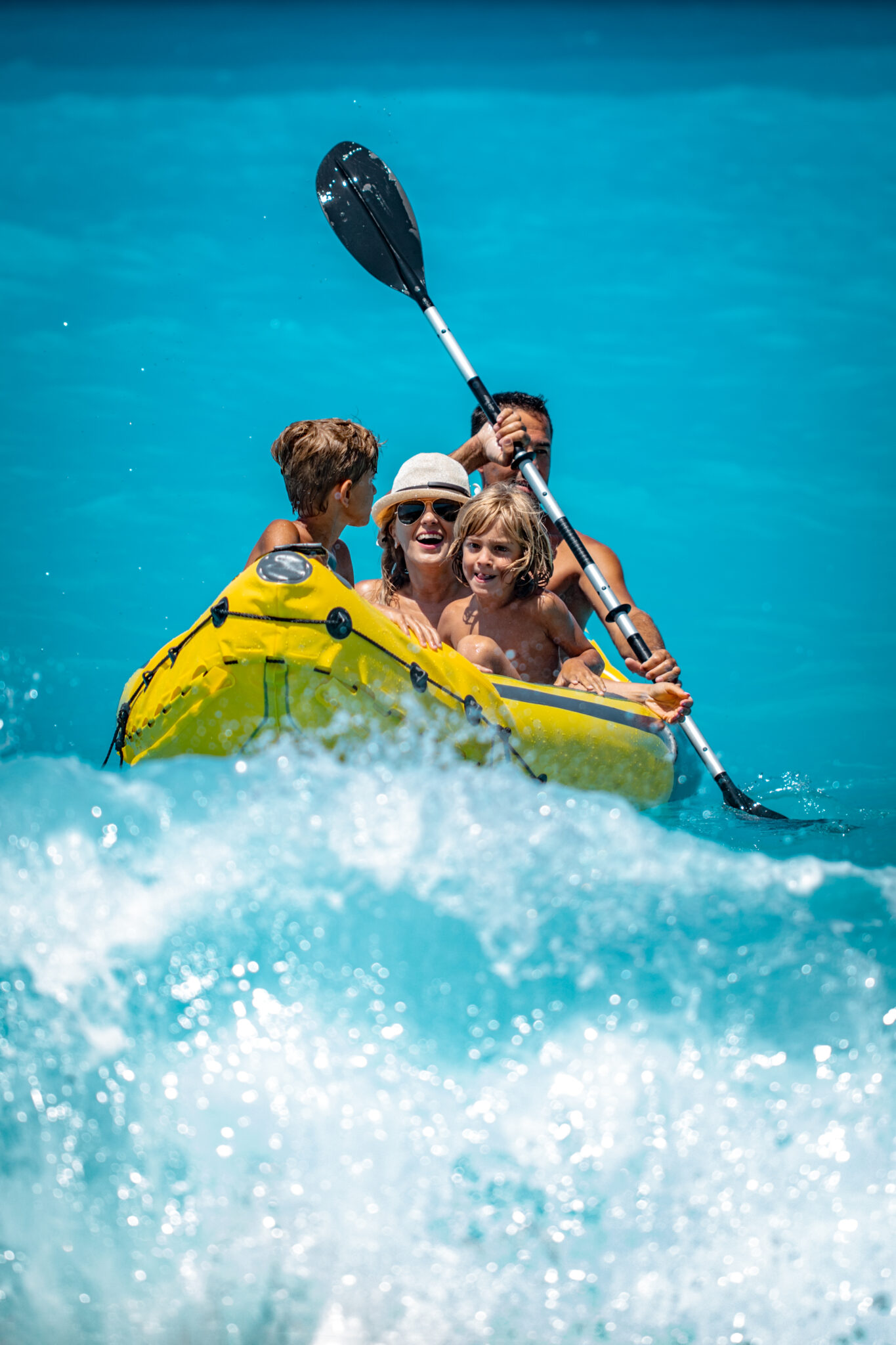 Happy family is enjoying paddling in yellow kayak at tropical ocean water during summer vacation.They are kayaking on the sea.