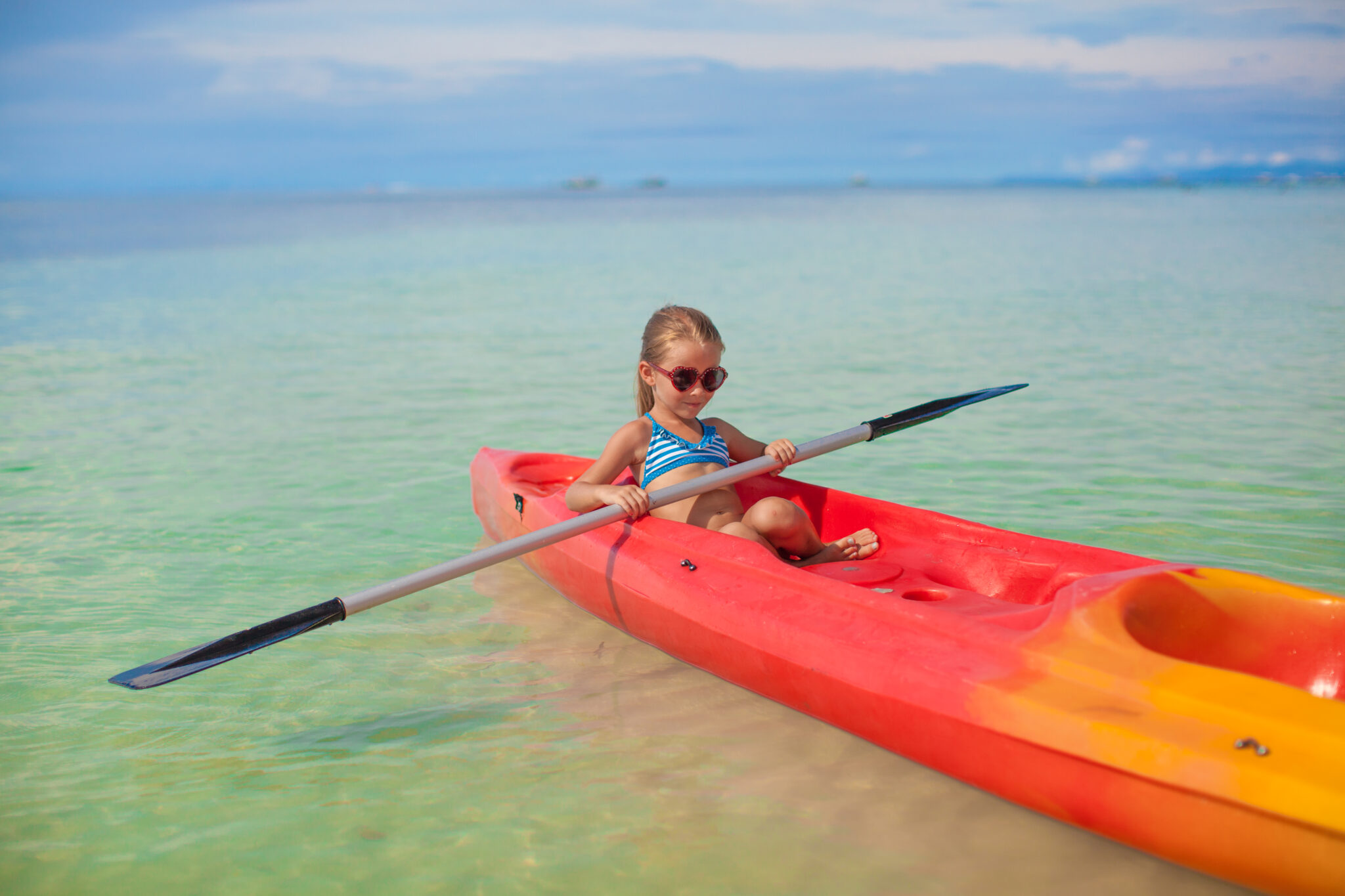 Little adorable girl rowing a boat in blue clear sea