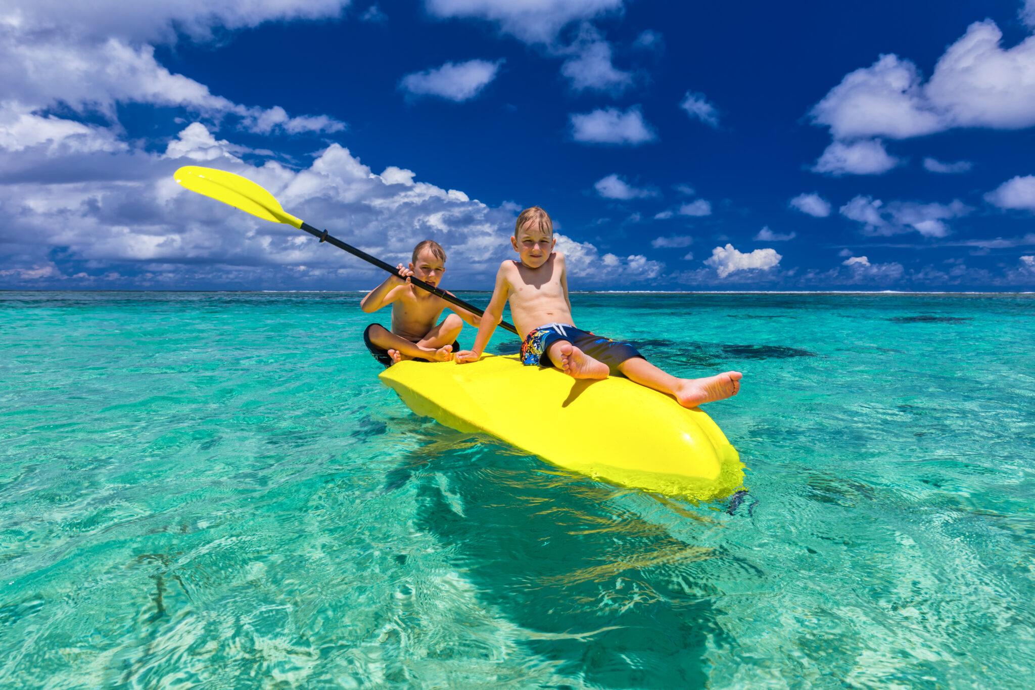 Two young shirtless caucasian boys kayaking at tropical sea on yellow kayak