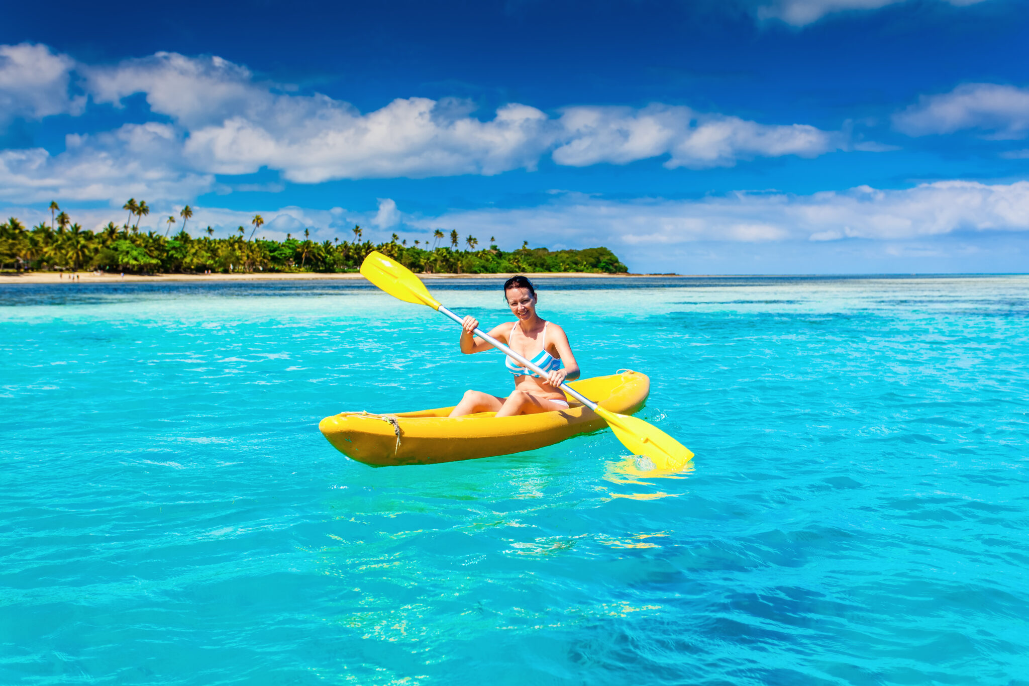 Woman Kayaking in the Ocean on Vacation in tropical Fiji island