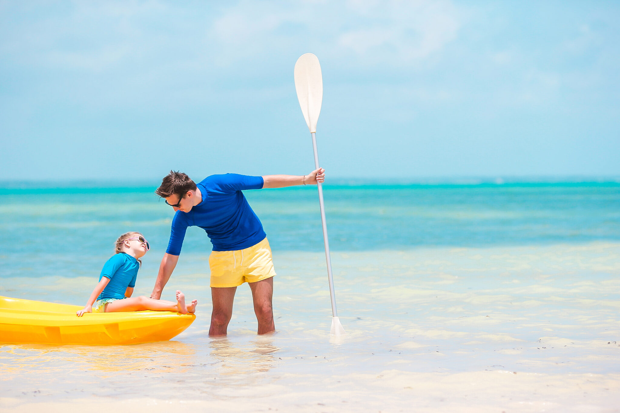 Young father andlittle daughter kayaking at tropical warm sea